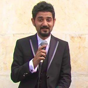 Сихан Эрсан в галстуке с микрофоном